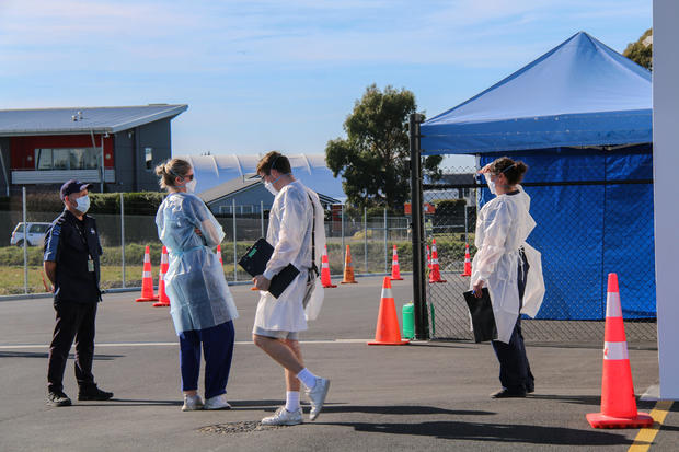 Staff members wearing face masks stand at a Covid testing