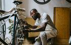 Male owner repairing bicycle in workshop