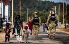 U.S. Military Police walk past Afghan refugees at the Village at Fort McCoy U.S. Army base