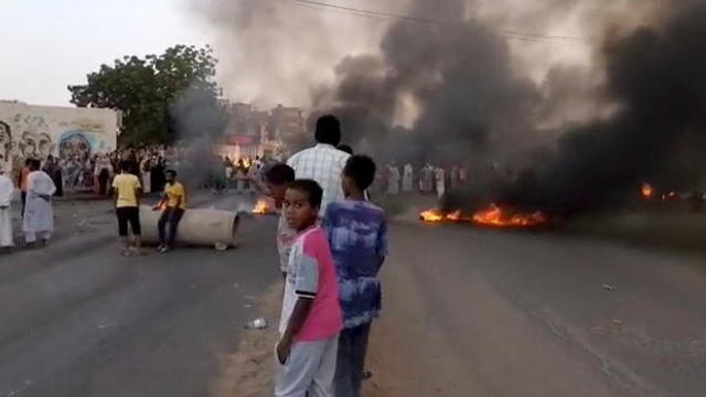 People gather around as smoke and fire are seen on the streets of Kartoum, Sudan, amid reports of a coup